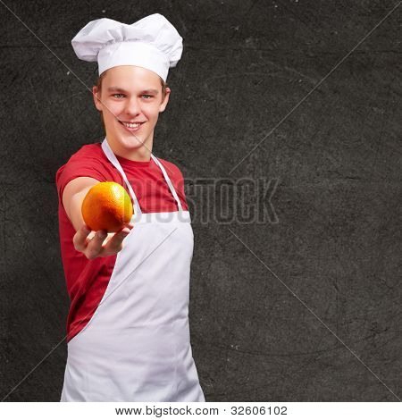 portrait of a young cook man offering an orange against a grunge wall