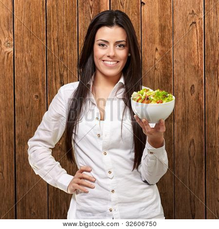 portrait of a young woman holding a salad against a wooden wall