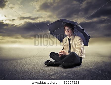 Young businessman under an umbrella with stormy sky in the background