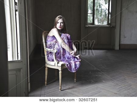 Beautiful woman sitting on an old chair in an empty room