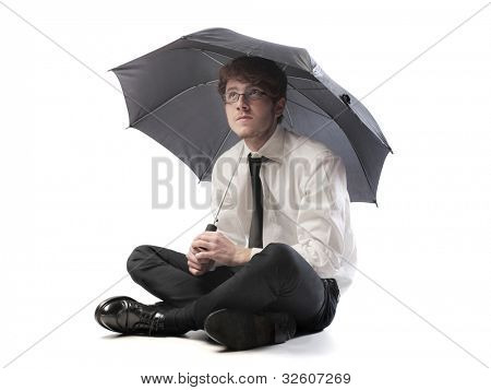 Isolated young businessman under an umbrella