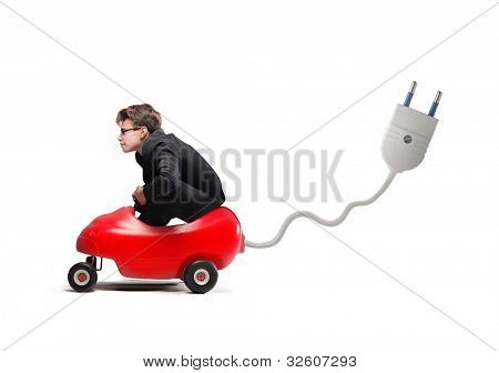 Young businessman driving an electric toy car