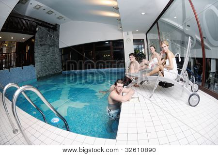 happy young people group have fun at swimming pool on spa and wellness center