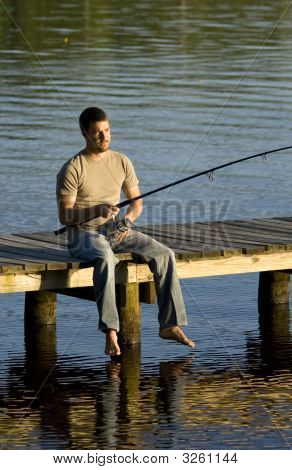 Man Fishing Off A Dock