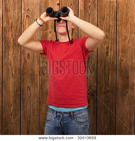 portrait of a young man with binoculars against a wooden wall