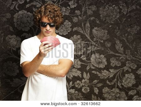 portrait of a young man wearing sunglasses and playing poker against a vintage background