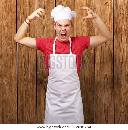 portrait of a young cook man wearing an apron doing an aggressive gesture against a wooden wall