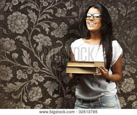 portrait of a young girl holding books against a vintage wall