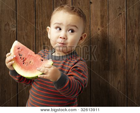 portrait of a handsome kid holding a watermelon and tasting it against a wooden background