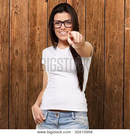 portrait of a young woman pointing with her finger against a wooden wall