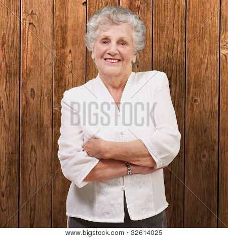 Portrait of ein liebenswert senior Woman stehend gegen eine Wand aus Holz