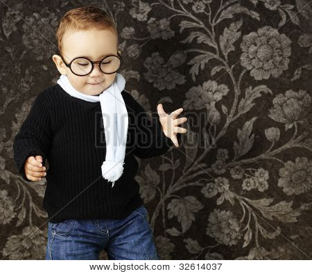 portrait of a kid wearing glasses looking down agaisnt a vintage background