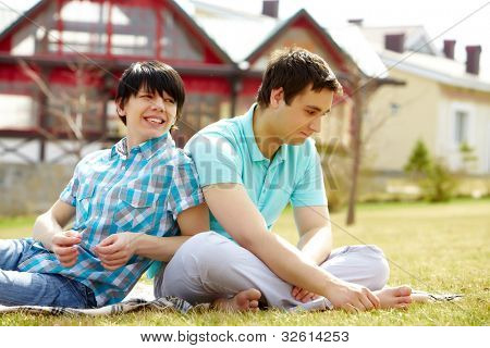 Young gays sitting together on the lawn enjoying warm weather