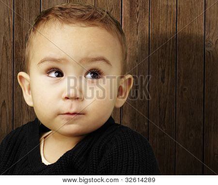 portrait of an adorable baby looking up against a wooden wall background