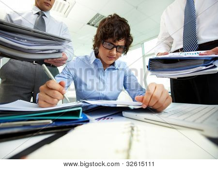 Terrified accountant doing financial reports being surrounded by businessmen with huge piles of documents