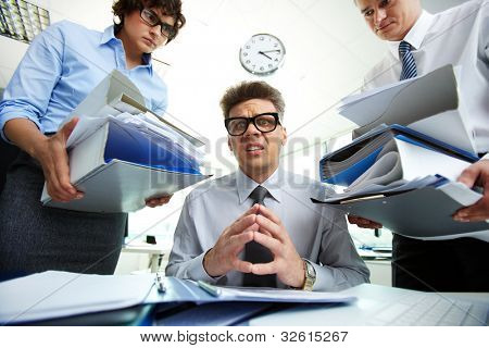 Terrified accountant looking at camera being surrounded by his partners holding huge piles of documents