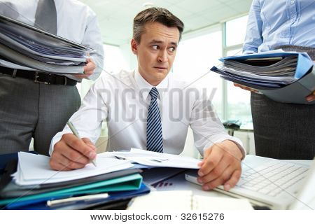 Shocked accountant looking at huge piles of documents while doing financial reports