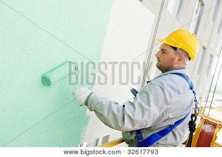 fachada de pintura de trabajador constructor del edificio con el rodillo de gran altura