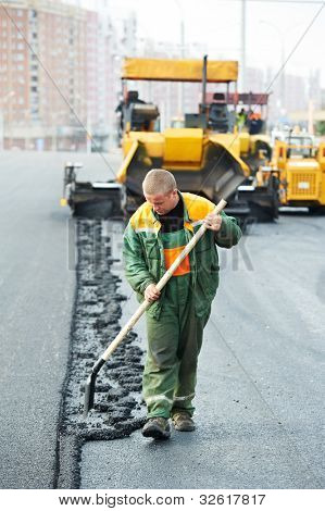 Worker with shovel in front of asphalt paver machine during road construction and repairing works