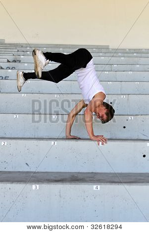 Portrait Of Athletic Male Doing Flip On Empty Stadium