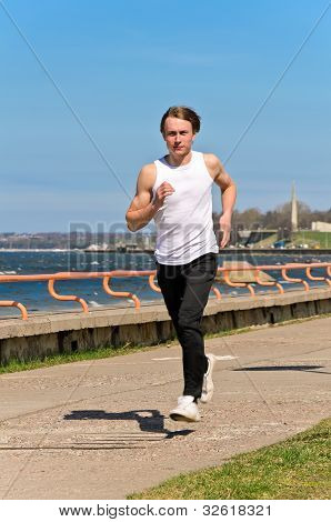 Athletic Young Male Running On The Shoreline