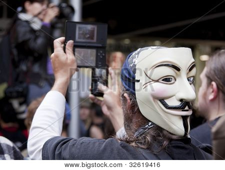 NEW YORK - MAY 1: A protester wearing a Guy Fawkes mask records the march to Union Square from Bryant Park on two mobile devices at Occupy Wall St 'May Day' protests on May 1, 2012 in New York, NY.