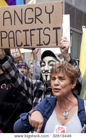 NEW YORK - MAY 1: A protester wearing a Guy Fawkes mask holds a sign that reads 'Angry Pacifist' during the march to Union Square at Occupy Wall St 'May Day' protests on May 1, 2012 in New York, NY.