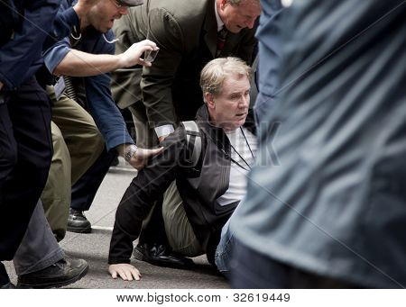 NEW YORK - MAY 1: A dazed man is helped to his feet after police attempt to guide protesters onto sidewalks during the march to Union Square during 'May Day' protests on May 1, 2012 in New York, NY.