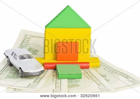 Model Of House And Car Standing On Money