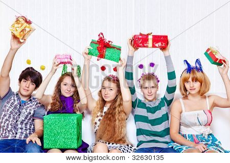 Happy teens sit on sofa with present boxes