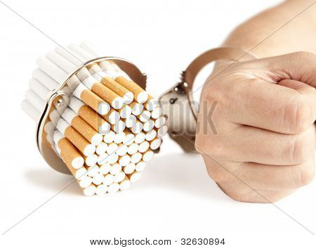 Cigarette and handcuffs isolateed on white