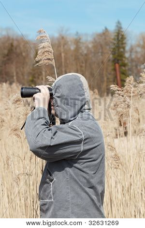 Man with binoculars watching the birds