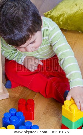 Little baby boy (2 years old) playing with toy blocks. Funny education