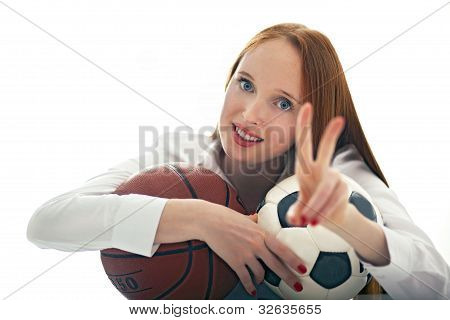 Attractive Girl Holding Soccer And Basketball Balls And Showing The Sign Of Victory