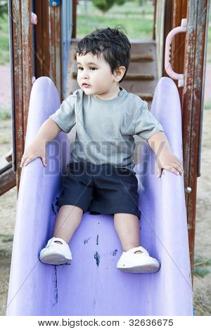 Cute baby playing on sliding board