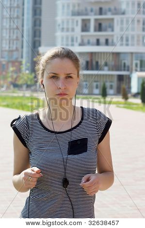 young beautiful woman listening music running in city