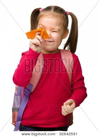 Portrait of little schoolgirl with backpack throwing a paper airplane, isolated over white