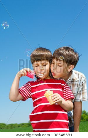 Boys blowing bubbles against blue sky