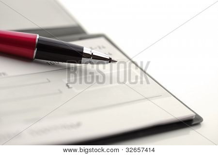 Blank cheque book with pen