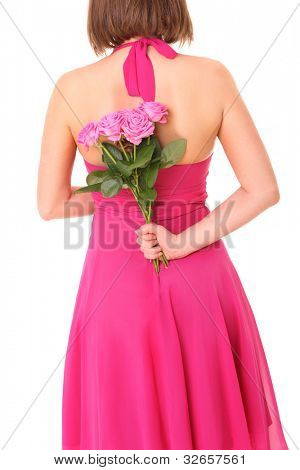 A picture of a young woman hiding a bunch of pink roses behind her back over white background