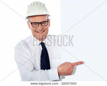 Senior Man In White Construction Helmet Holding Placard