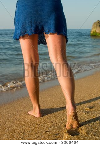 Legs In Blue Skirt Going To The Sea