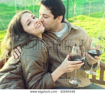 Happy Couple Drinking Red Wine Outdoor. Young Man Kissing Laughing Girl
