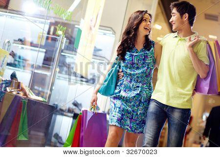 Vestida casualmente belo casal andando pelo shopping carregando um monte de sacos de compras