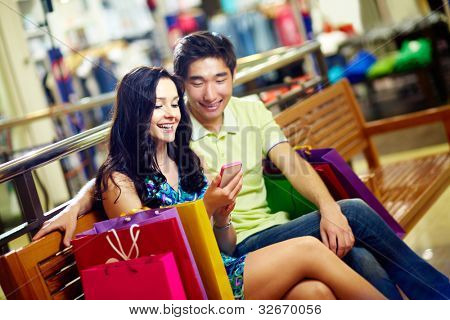 Tilt up of a happy couple using the mobile for quick and convenient communication in shopping mall
