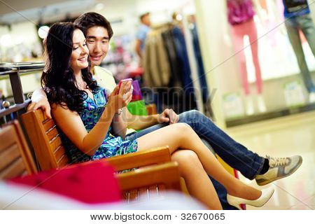 Young people using a smart phone in the shopping mall, shopping series
