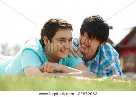 Amantes gays felices tumbado en el césped