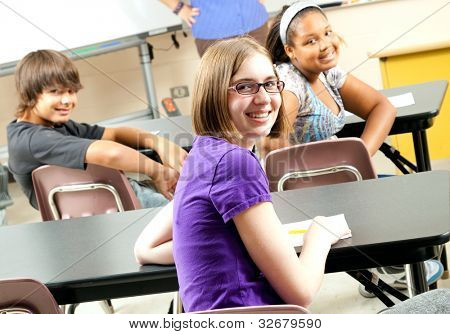 Happy teenage middle school or highschool students in class.