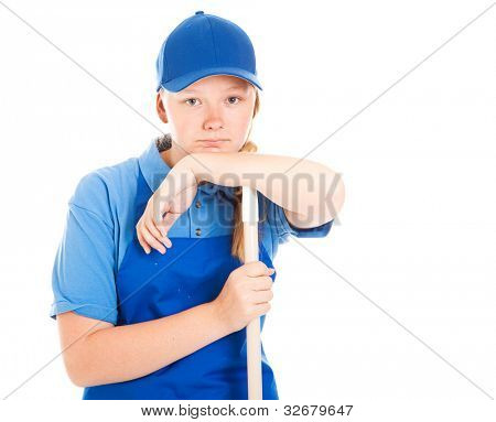 Teenage girl in a work uniform, leaning on a mop or broom handle and looking bored and unhappy.  Isolated on white.