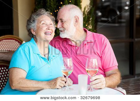 Senior couple at a cafe, enjoying wine and conversation together.